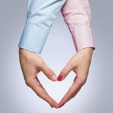 Man and woman make a shape of a heart with hands. Man and woman holding hands in a shape of a heart  isolated on whitebackground. Young couple in love Royalty Free Stock Photos