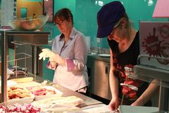 Two woman busy In kitchen stock photography