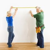 Man and woman measuring wall. Stock Photos