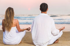 Man and woman meditating in front of sea Royalty Free Stock Photography