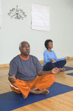 Man And Woman Meditating In Lotus Position Stock Photo