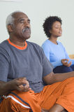 Man And Woman Meditating In Lotus Position. An African American senior men and women meditating in lotus position Stock Photography