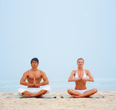 A man and a woman meditating together on the beach Royalty Free Stock Photo