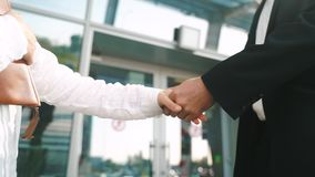 Man and woman meeting on the street and shaking hands smiling in the street
