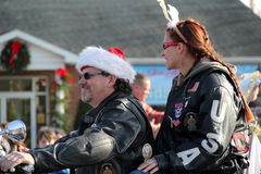 Man and woman on motorcycle in procession of Annual Holiday Parade,Glens Falls,New York,2014. Joyful image of man and woman in holiday hats on motorcycle,during royalty free stock photos