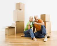Man and woman with moving boxes. Middle-aged couple sitting on floor among cardboard moving boxes with coffee Stock Photos