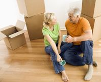 Man and woman with moving boxes. Middle-aged couple sitting on floor among cardboard moving boxes drinking coffee Royalty Free Stock Image