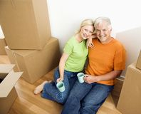 Man and woman with moving boxes. Middle-aged couple sitting on floor among cardboard moving boxes with coffee Stock Photo