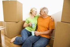 Man and woman with moving boxes. Middle-aged couple sitting on floor among cardboard moving boxes drinking coffee Stock Photos