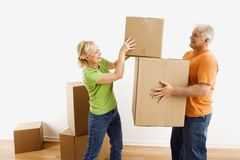 Man and woman moving boxes. Stock Images