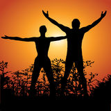 Man and woman in nature. A man and a woman's silhouettes outside against the sunset Royalty Free Stock Image
