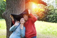 Man and the woman near an oak hide from a rain in the summer day Stock Images