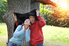 Man and the woman near an oak hide from a rain in the summer day Royalty Free Stock Image