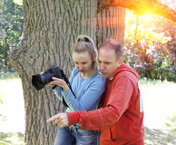 Man and  woman near an oak in summer  day show to the side and looked scaredly and  photograph on the big camera Royalty Free Stock Photography