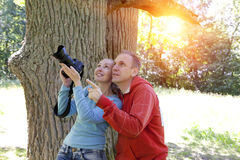 Man and  woman near an oak in summer  day show to the side and photograph on the big camera Stock Image