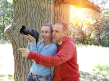 Man and  woman near an oak in summer  day show to the side and photograph on the big camera Royalty Free Stock Photos