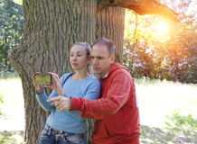 Man and  woman near an oak in summer  day show to the side and photograph on phone Royalty Free Stock Photo
