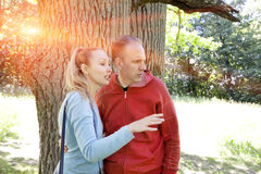 Man and  woman near an oak in summer  day show to the side Stock Images
