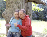 Man and  woman near an oak in summer  day show to the side Stock Photo