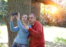 Man and  woman near an oak in summer  day show up and photograph on phone Royalty Free Stock Photography