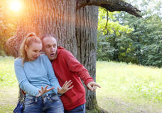 Man and  woman near an oak in summer  day something was seen aside and looked scaredly and with astonishment Royalty Free Stock Photos