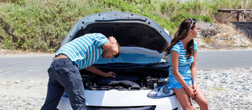 Man and woman near their broken car. Stock Photo