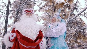 Man and woman in New Year costumes on Christmas Eve are happy to see the gifts stock video