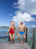 The man and the woman in New Year's Santa-Klaus cap jumps on background of sea Stock Photography