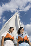 Man and Woman Next to Sailboat on Water - Vertical. A woman and man are next to a sailboat.  They are smiling and looking away from the camera.  Vertically Stock Images