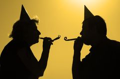 Man and woman with noise-makers. On the party Stock Image