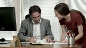 Man and woman at the office contract discussion signature dolly out stock footage
