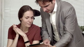 Man and woman at the office data on tablet discussion.  stock footage