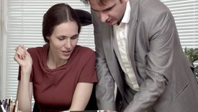 Man and woman at the office data on tablet discussion stock footage