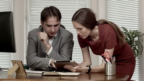Man and woman at the office data on tablet discussion dolly out.  stock footage