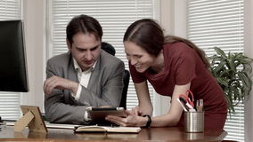 Man and woman at the office data on tablet discussion dolly out stock video footage