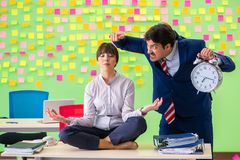 The man and woman in the office with many conflicting priorities in yoga concept Royalty Free Stock Image
