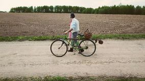 A man and a woman in old clothes are walking along the road with a bicycle and baskets. stock footage