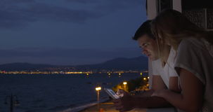 Man and woman with pad on balcony at night. Young couple using tablet computer on the balcony in hotel at the seaside. View to the waterfront and sea at night stock video