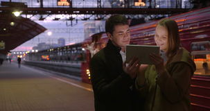 Man and woman with pad at the station. Young couple at the railway station in the evening. They using tablet computer, train at stop in background stock video footage