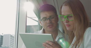 Man and woman with pad talking about business. Businesspeople in glasses discussing some issue using tablet computer. They having a talk in the office by window stock video