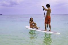 Man and woman on paddle board. Hawaiian beachboy with girl in bikini on paddle board in hawaii Stock Photography