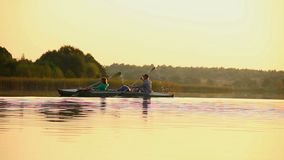 Man and woman paddling boat synchronously. Team-building, sport. Stock footage stock video