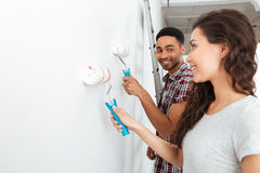 Man and woman painting wall. Smiling mulatte men making repair and looking at women while she painting wall  over white background Stock Photos