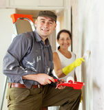 Man and woman paints wall Stock Photo