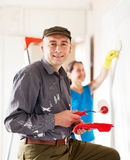 Man and woman paints wall Stock Photography