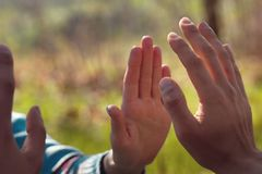 Man and woman palms almost touching on natural blurry background enlighten by sun. Practice of energy feeling, perception and transmission royalty free stock image