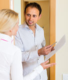 Man and woman with papers at doorway Royalty Free Stock Photography