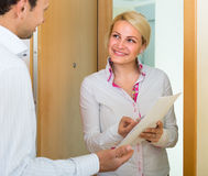 Man and woman with papers at doorway. Smiling female agent asking tenant to sign a document at doorway Royalty Free Stock Photo
