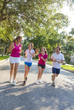 Man Woman Parents Girl Children Family Running or Jogging. A fit happy and healthy family, man, woman, mother, father parents and two girl children road running Royalty Free Stock Photo