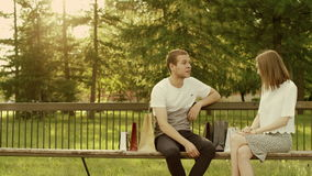 Man and woman in the park. Man and woman sit on the bench in the park talking to each other stock video footage